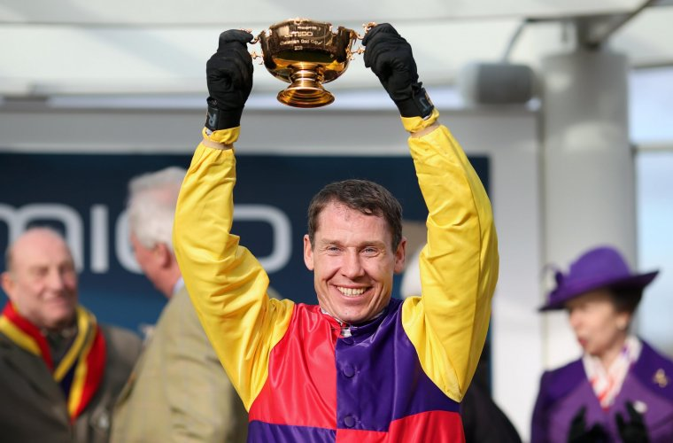 Richard Johnson holds the Gold Cup Trophy aloft after winning the Gold Cup On Native River